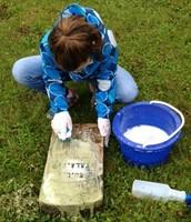 Samantha Resler scrubs Marcus Dillender's headstone
