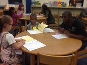 Mr. Williams listening to 1st graders talk about their data.