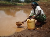 A woman struggling to filter the water!