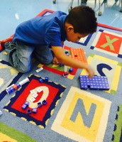 Donovan building his Brain Book words with letter blocks
