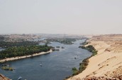 The Nile River with sand and grass around it.
