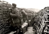 German Soldiers look out over their trench wall.