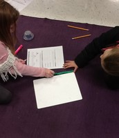 Students use centimeter cubes to measure a paper.