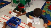 Alyssa and Mason are identifying their apples' shape and drawing a picture of it!