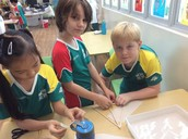 3TCo working collaboratively to construct hang gliders for their Ewok friends.
