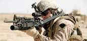 Soldier aiming down the scope of an M16a3 rifle