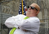 Larry Hogan relaxing by a flag and a barbed wire fence