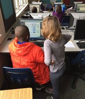 Two students helping each other use the website.
