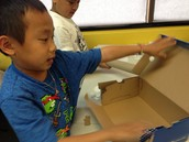 Ethan examining the shoe box to plan his diorama