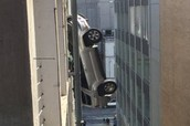 Teen driver ends up dangling off the side of a building
