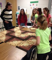 Examining the details of each quilt square.