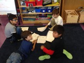 2nd graders conferring to check math work