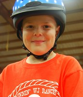 "Abby's brother, Tye, smiling for the camera as he prepares to ""show off"" his riding skills in the big arena."