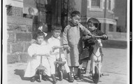 Four Oriental children with bicycles