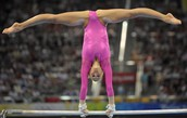 this is a gymnast doing a stradel spit on the bars
