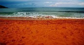 What makes the sand of Kaihalulu Bay red?
