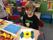 Build a pattern block design using a line of symmetry...