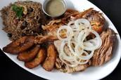 El cerdo asado con arroz,frijoles, y los plátanos