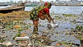 A Bangladeshi woman collects water for use on the polluted river Buriganga in Dhaka.