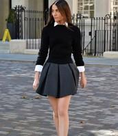 une jupe grise en coton et un chemisier noir  à manches longues en cotton