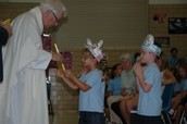 Kindergarten receiving their blessed Religion textbooks