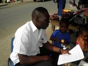 Olumuyiwa Kotila - a Literacy Fellow, while gathering environmental data from a market woman in Agbowo community