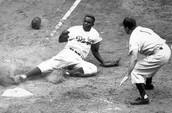 Robinson sliding onto home base.