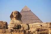 This is a sphinx with a pyramid in the background