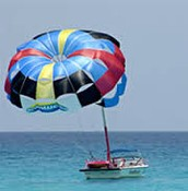 A parachute gaining wind as someone prepares to parasail