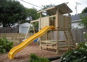 Custom built playset within fully enclosed wooden privacy fenced backyard.