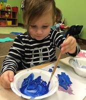 Caroline painting a mitten masterpiece.