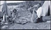 Ojibwe people mending fishing net.