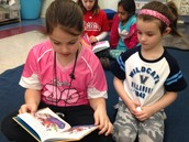 Catherine and her buddy reading on the carpet