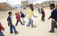 Kids play soccer in the street...