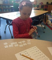 Abigail using Earth counters to subtract.