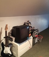 My guitar, VHS tv player, and my mini fridge with a basketball hooked on the front