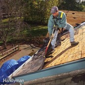 Jose peeling shingles off a garage roof.