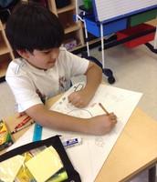 Rodrigo carefully coloring his math poster