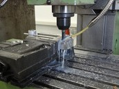 Taladro de columna haciendo un agujero en un metal, utilizando taladrina para refrigerar la pieza