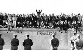The people of Berlin riot for freedom against the Berlin Wall.