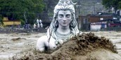 Lord shiva's statue being carried away in the flood.
