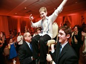 Doing the hora dance with people holding the person up in the air on a chair