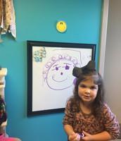"""New Center...dry erase board!  Ella's """"self portrait""""!"""