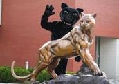School mascot standing behind the Adelphi statue