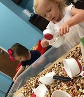 Caroline and Addison play with beans.