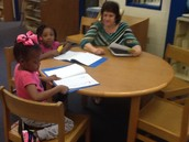 Kindergarten students explain what they have learned to Mrs. Patrick.