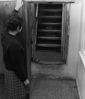 Hidden staircase in Anne Frank House  A woman stands in a hallway holding open a bookcase mounted on hinges, behind which is visible a staircase hidden in the Anne Frank House, Amsterdam, Netherlands, 1960s. (Photo by Anne Frank Fonds - Basel/Anne Frank House - Amsterdam/GettyImages)