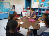 Small group instruction by Abby Edwards with her students able to reference an anchor chart nearby (#9 Using Learning Tools-Anchor Chart)