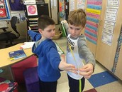 Collin makes sure the tape measurer is lined up exactly next to Ben's middle finger so he can get an exact measurement of Ben's arm span!