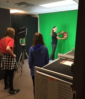Mrs. Colin's MDGOT class advertising their product in the green screen room